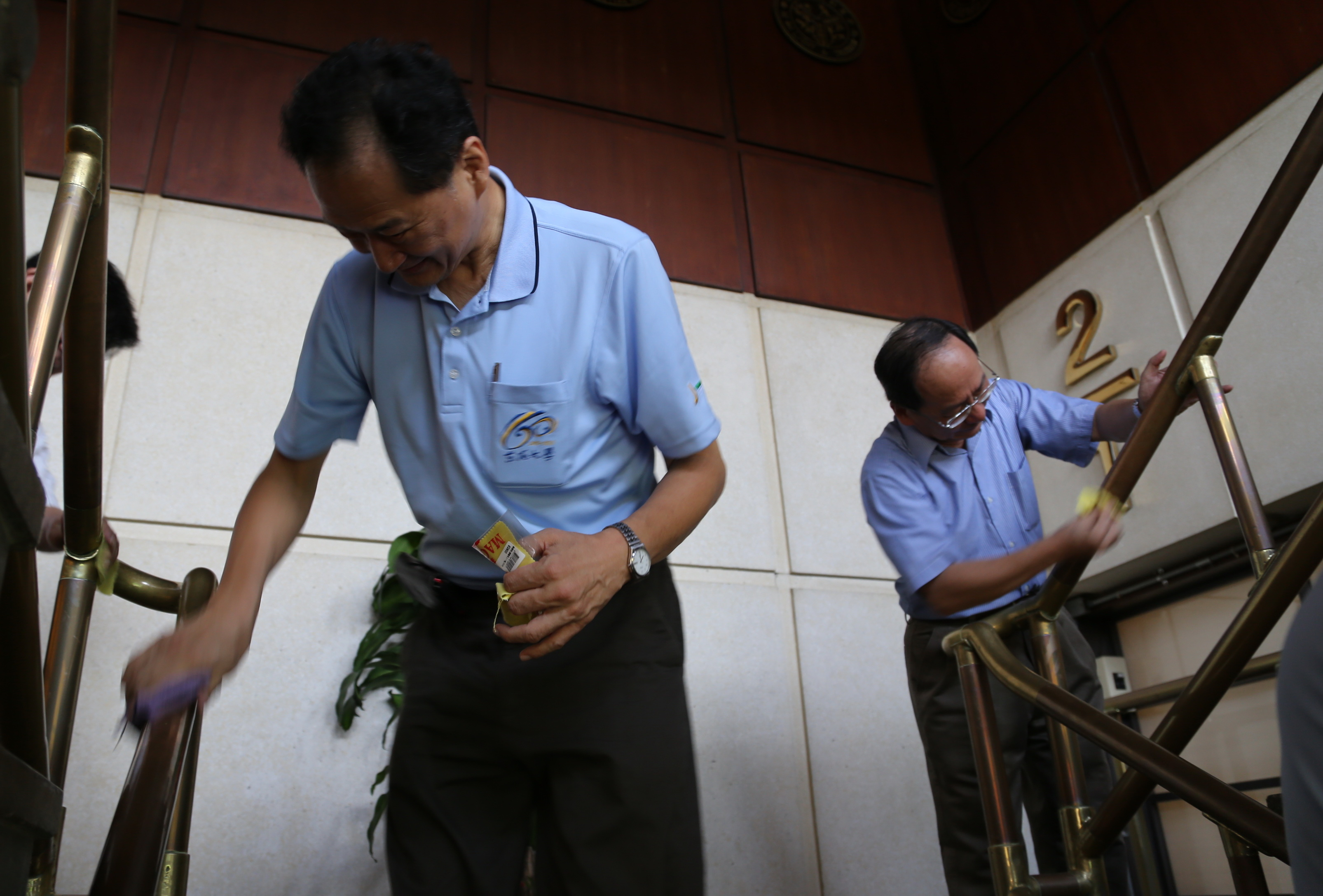 Yuan Zhuping, President of Tunghai University Alumni, and Wang Maojun, President of the University, wipe the office railing