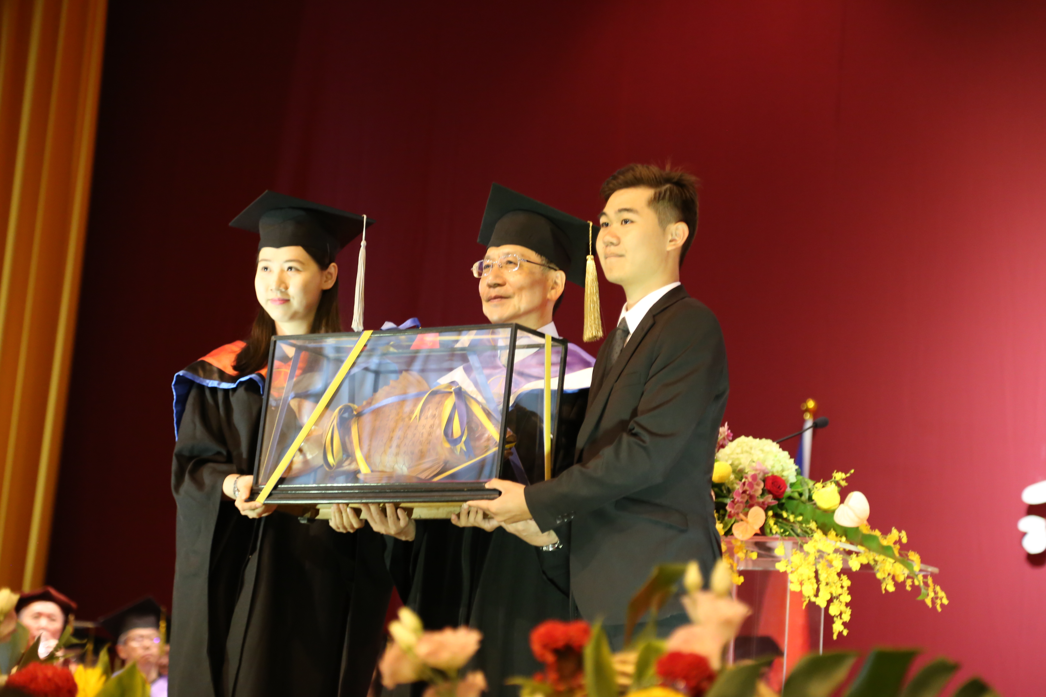 Tunghai University passed the fire in the witness of Wang Maojun, the president of the Association of Bilian, Huang Lizhen (left), who passed the wooden fish to the student president Chen Xinxiu